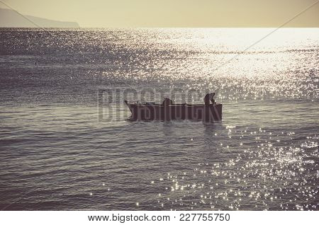Fisherman At Sunset In The Waters Of The Gulf Of Naples