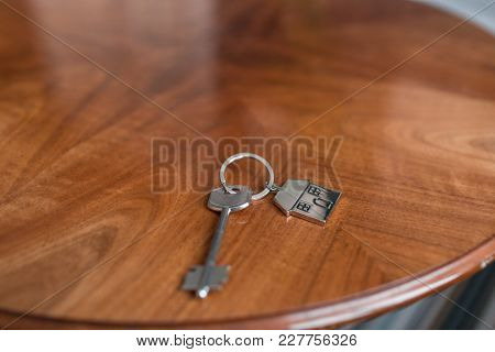 House Key And Keychain In The Form Of Homes Lies On Wooden Table. Concept For Real Estate, Mortgage,