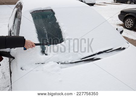 Womens Hand With Snow Brush Clean Car Windshield From Snow