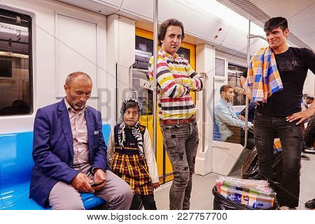Tehran, Iran - April 29, 2017: Iranian Men And A Little Girl In A Religious Veil Ride In A Subway Ca