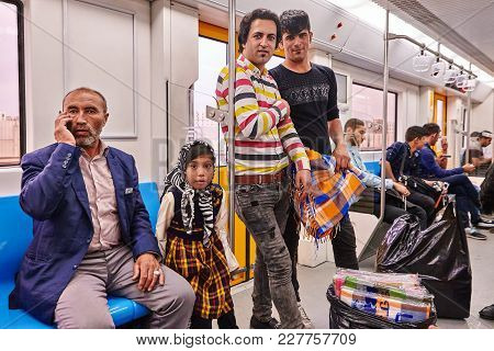 Tehran, Iran - April 29, 2017: Iranian Men And A Girl In A Hijab Ride On A Subway Train, An Elderly