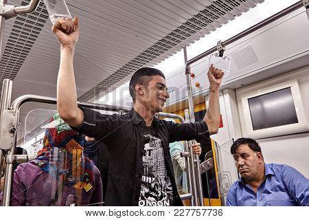 Tehran, Iran - April 29, 2017: Iranian Man Rides Underground Train And Holds The Rail.