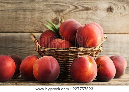 Sweet Nectarines In Basket On Grey Wooden Table