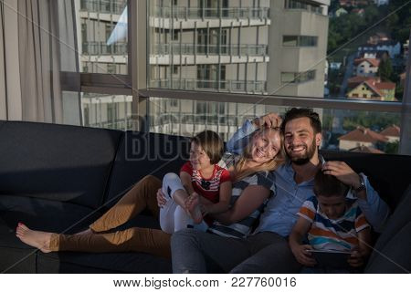 happy couple spending time with kids using tablet computer on sofa at home