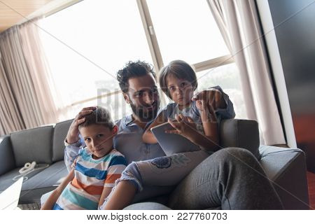 happy father spending time with kids using tablet computer on an armchair  at home