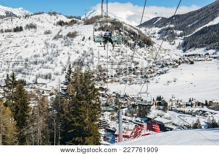 La Thuile, Italy - Feb 18, 2018: Chairlift At Italian Ski Area On Snow Covered Alps And Pine Trees D