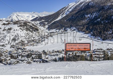 Signpost Written In Various Languages Warning Of Expert Ski Run Ahead. View Of Thuile Town In Valley