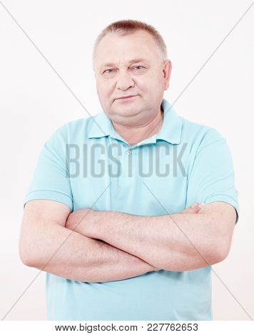 Portrait of aged man wearing blue polo shirt standing with crossed arms against white wall - retirement concept