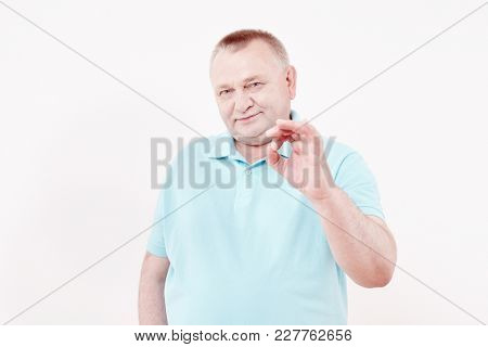 Mature cheerful man wearing blue shirt showing A-ok hand gesture and smiling against white wall - success concept