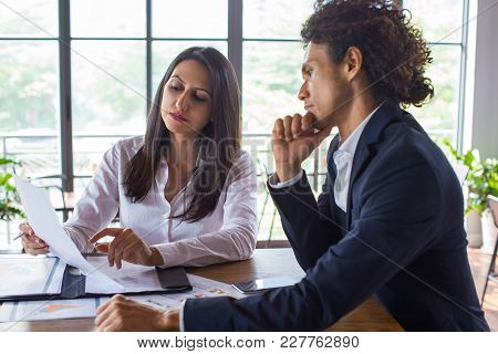 Pensive Business Executives Focusing On Financial Report. Concentrated Business Partners Discussing