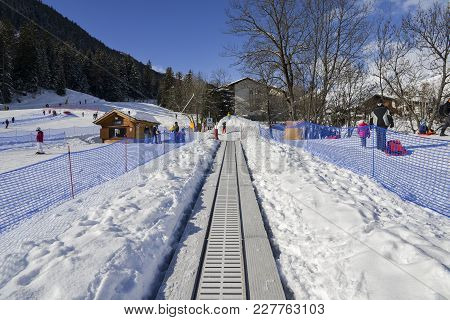 Ascending Conveyor Belt To A Beginners Run For Children And Parents In Ski Resort With Mountains In