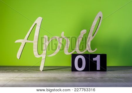 Happy Easter. April 1st. Day 1 Of Month, Calendar On Wooden Table And Green Background. Spring Time.