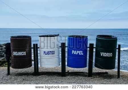 Recycling Bins Of Different Colors On The Beach That Says: Organic = Organic, Plastic = Plastic, Pap