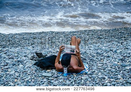 Man Reading The Newspaper On The Beach And Enjoying The Summer