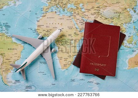 Airplane And Two Passports Travel Documents On The Map Of The World, Holidays Abroad. Plane Worldwid