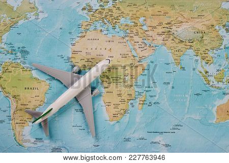 White Toy Plane On The World Map Background. Traveling, Tourism, International Flights With Flying A