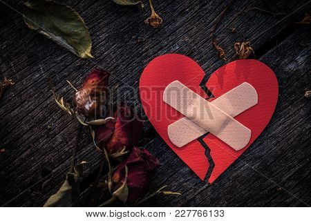 First Aid Band Cushioned Plaster Strip Medical Patch Glued On Red Heart With Dried Red Rose On Woode