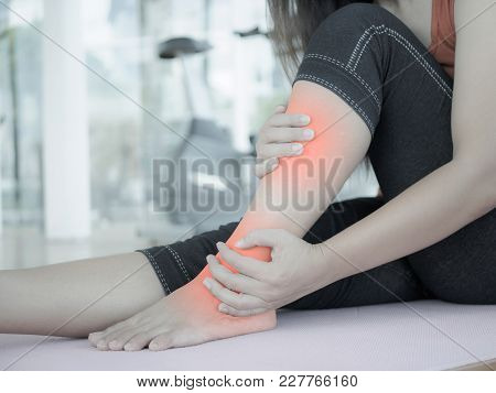 Unhappy Woman Sitting On The Yoga Mat With Ankle  Injury, Feeling Pain. Health Care And Execise Conc