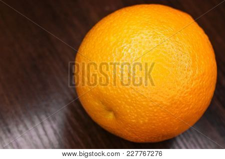 Large Orange On A Wooden Background.