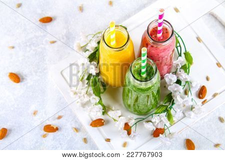 Green, Yellow, Purple Smoothies In Currant Bottles, Parsley, Apple, Kiwi, Orange On A Gray Table Wit