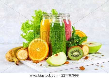 Green, Yellow, Purple Smoothies In Currant Bottles, Parsley, Apple, Kiwi, Orange On A Gray Table