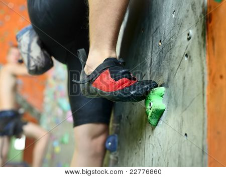 Young man's foot climbing indoor wall