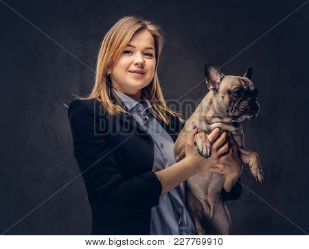 Portrait Of A Blonde Businesswoman In A Formal Suit Holds A Cute Pug.