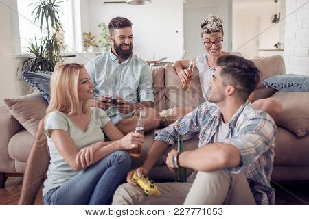 Friends Having Fun And Playing Video Games At Home.