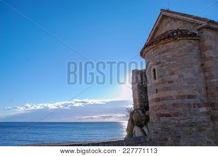 Ancient Tower By The Sea Against A Clear Blue Sky