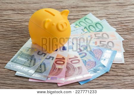 Yellow Piggy Bank On Pile Of Euro Banknotes On Wooden Table, Financial Savings Money Account Or Euro
