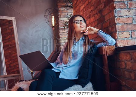 Portrait Of Charming Brunette Businesswoman In Glasses And Blue Shirt Working Online With Laptop And