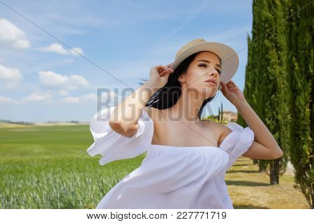 Woman is walking along the road among the fields and a typical Tuscan landscape behind her. Tuscany, Italy