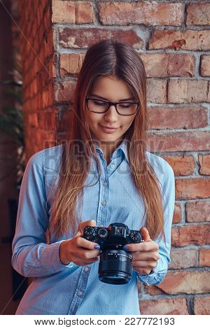 Portrait Of A Young Female Photographer In Glasses And Blue Shirt Leaning Against On A Brick Wall In