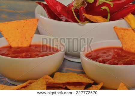 Chili Corn-chips With Salsa Dip And Chili Peppers On Wooden Background.