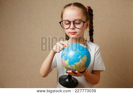 A Little Girl With Glasses Is Looking For A Place On The Globe