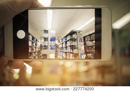 Student Man Hand Holding Mobile Smart Phone, Cellphone Over Blur Library Book Shelf Natural Backgrou