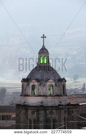Guamote, Ecuador Catholic Church Spire With Cross, With Green Glowing Stained Glass Windows