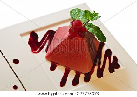 Red Cheesecake With Berries And Syrup On A White Background