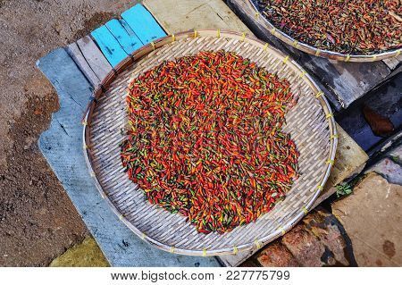 Chilli Peppers On A Braided Wooden Tray In A Market. Laos. Close Up.