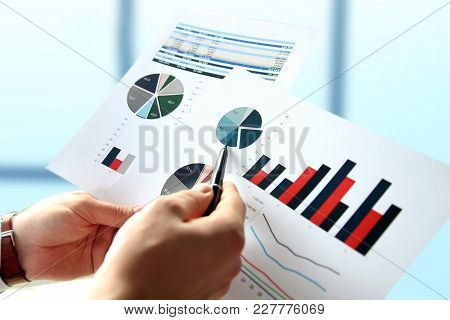 Business Man Working And Analyzing Financial Figures On A Graphs