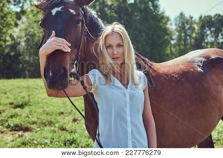 Charming Beautiful Blonde Wearing A White Blouse And Jeans Hugging A Horse To A Green Field.