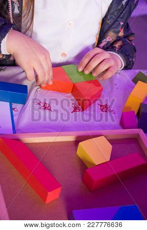 Hand Holding Colorful Wooden Puzzle Element In Hand