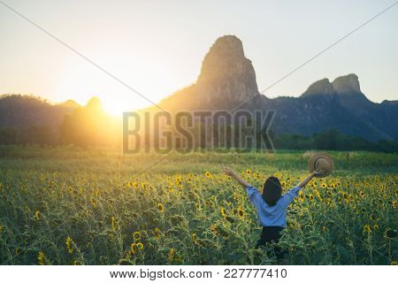 Young Woman Traveler With Hat In Sunflower Fields With Happiness And Cheerful At Sunset And Arms Rai