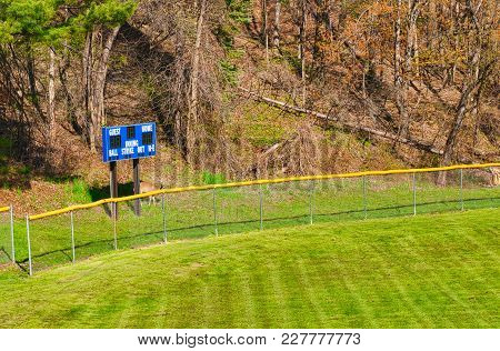 A Small Scoreboard By The Outfield Of A Village Baseball Field, With Deer Lurking Underneath