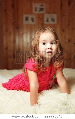 Red-haired Girl In A Pink Dress Sitting On The Bed. Portrait The Cute Child Of Two Years.