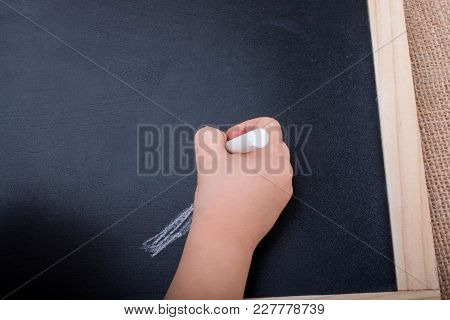 Hand Holding  White Chalk And Black Board