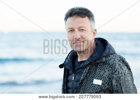 Handsome middle-aged man at the beach. Attractive happy smiling mid adult male model posing at seaside, sunset o sunrise. Outdoor portrait of beautiful man.