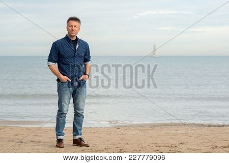 Handsome middle-aged man walking at the beach. Attractive mid adult male model posing at seaside in blue jeans, t-shirt shirt. Full-length outdoor portrait of beautiful macho man.