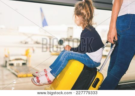 Mom Carries Your Luggage With Happy Baby At The Airport Terminal. Flying For Holliday, Traveling Wit