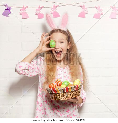 Easter celebration. Child is holding a basket with Easter eggs.